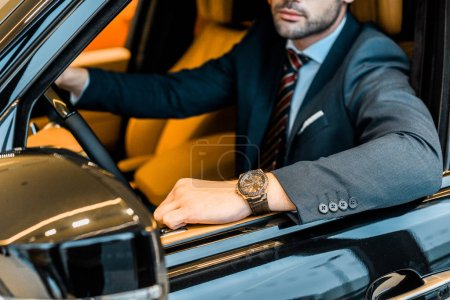 partial view of businessman with luxury watch sitting in automobile