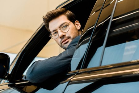 selective focus of stylish businessman in eyeglasses looking out from window of car