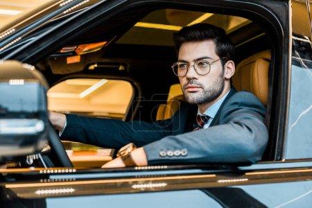 young stylish businessman in eyeglasses sitting in luxury car