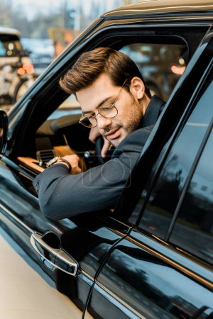 selective focus of stylish businessman in eyeglasses looking out from window of automobile