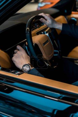 Photo pour Cropped image d'homme d'affaires avec des montres de luxe assis dans l'automobile - image libre de droit