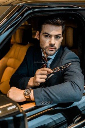 Photo pour Bel homme d'affaires avec des montres de luxe tenant des lunettes tout en étant assis dans la voiture - image libre de droit