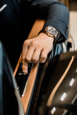 Photo pour Image recadrée de l'homme d'affaires avec des montres de luxe en poussant le bouton de fermeture de fenêtre d'automobile - image libre de droit