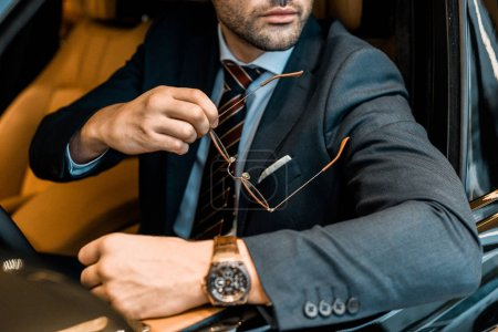 Photo for Partial view of businessman with luxury watch holding eyeglasses while sitting in car - Royalty Free Image