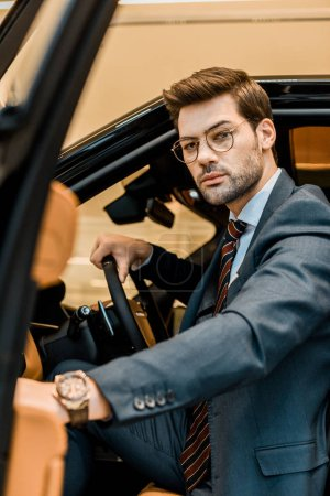 serious businessman closing door while sitting in automobile