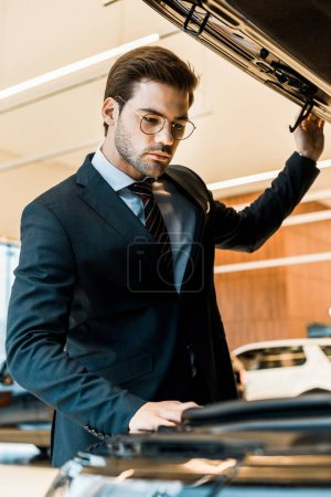 Photo pour Vue faible angle d'homme d'affaires en lunettes de vue à la recherche à l'intérieur du capot de la voiture ouverte d'automobile noir - image libre de droit