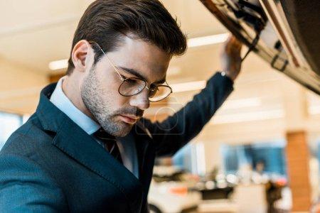Photo pour Bouchent la vue de l'homme d'affaires de lunettes à la recherche à l'intérieur du capot de la voiture ouverte d'automobile noir - image libre de droit