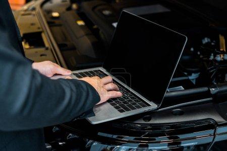 Foto de Vista parcial del empresario comprobar capilla del coche con el ordenador portátil con pantalla en blanco - Imagen libre de derechos