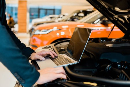 Photo pour Cropped image d'homme d'affaires contrôle le capot de la voiture avec ordinateur portable avec écran blanc - image libre de droit