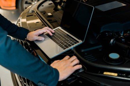 Photo pour Vue partielle de l'homme d'affaires contrôle le capot de la voiture avec ordinateur portable avec écran blanc - image libre de droit