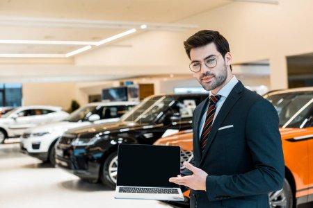 Photo pour Heureux concessionnaire de voiture mâle dans les lunettes pointant vers un ordinateur portable avec écran blanc dans le salon de la voiture - image libre de droit