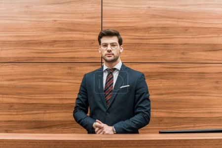 Photo pour Bel homme d'affaires en lunettes permanent à la réception de bureau moderne - image libre de droit