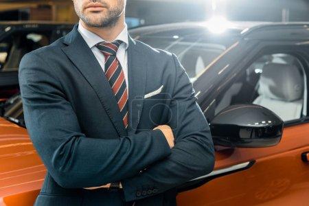 Photo pour Vue partielle de l'homme d'affaires posant avec les bras croisés près automobile - image libre de droit