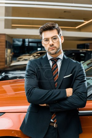 confident businessman in eyeglasses posing with crossed arms near automobile