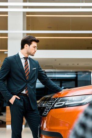 Photo pour Vue latérale de bel homme d'affaires dans les lunettes en choisissant la voiture dans le salon de concession - image libre de droit