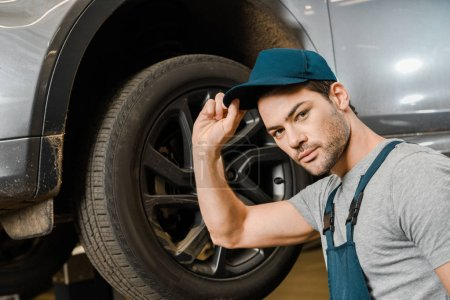 Photo for Portrait of male auto mechanic in working overall posing near car at repair shop - Royalty Free Image