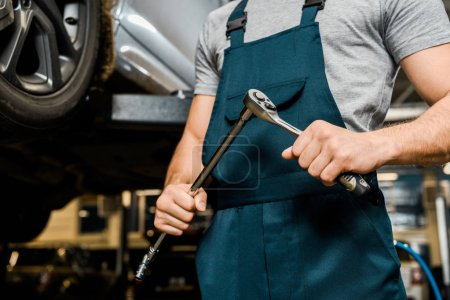 cropped shot of auto mechanic with lug wrench in hands at mechanic shop