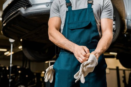 partial view of auto mechanic in uniform wearing protective gloves at auto repair shop