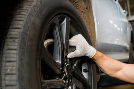 cropped shot of repairman in protective glove examining car wheel at auto repair shop