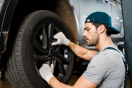 side view of auto mechanic in protective gloves checking automobile wheel at auto repair shop
