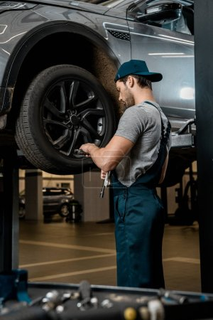 auto mechanic in uniform fixing car wheel at auto repair shop