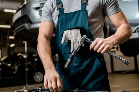 partial view of auto mechanic in uniform with lug wrench at auto repair shop