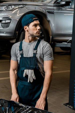 young repairman standing at tabletop with mechanic tools at auto repair shop