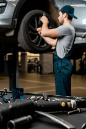 selective focus of auto mechanic in uniform fixing car wheel at auto repair shop