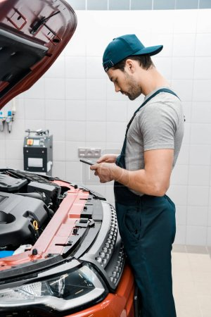 auto mechanic in uniform using smartphone at car with opened cowl at mechanic shop