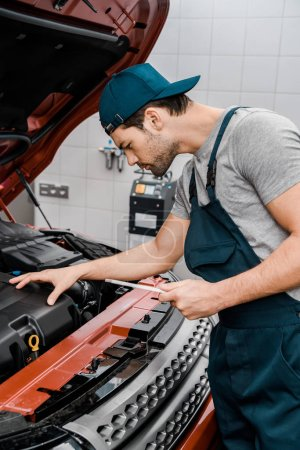 side view of auto mechanic with tablet checking car cowl at mechanic shop