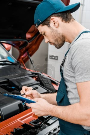 Photo for Side view of repairman with notepad examining car at auto repair shop - Royalty Free Image
