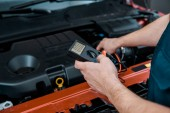 partial view of auto mechanic with multimeter voltmeter checking car battery voltage at mechanic shop