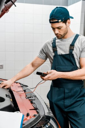 Photo pour Jeune mécanicien automobile avec multimètre voltmètre vérifier la tension de la batterie de voiture à l'atelier de mécanique - image libre de droit