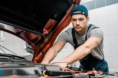 portrait of young auto mechanic with multimeter voltmeter checking car battery voltage at mechanic shop
