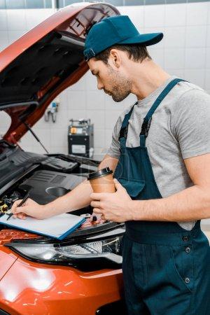 Photo pour Mécanicien automobile avec gobelet jetable de café notes chez les automobiles avec capot ouvert - image libre de droit