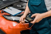 cropped shot of auto mechanic holding multimeter voltmeter for car battery voltage checking at mechanic shop