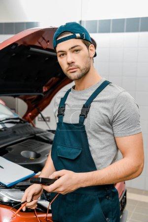 Photo pour Portrait du voltmètre multimètre de tenue de mécanicien automatique pour le contrôle de tension de batterie de voiture à l'atelier de mécanicien - image libre de droit