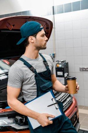 Photo pour Mécanicien pensif avec café pour aller et bloc-notes s'appuyant sur la voiture avec le capot ouvert à l'atelier mécanique - image libre de droit
