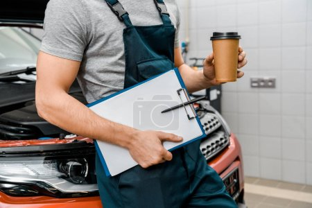 partial view of male auto mechanic with notepad and coffee to go near car at auto repair shop