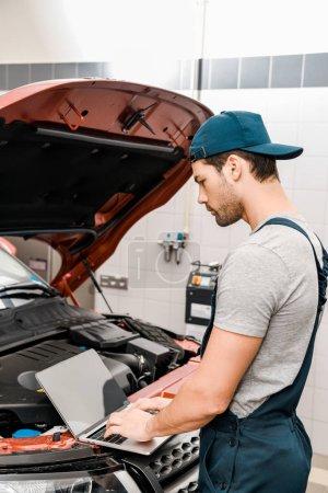 Photo pour Vue latérale du travail mecanicien auto sur portable chez les automobiles avec le capot de la voiture ouverte à l'atelier mécanique - image libre de droit