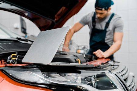 Photo pour Mise au point sélective d'ordinateur portable et auto mécanicien à l'atelier de réparation automobile - image libre de droit