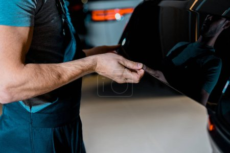 cropped shot of auto mechanic checking car trunk at auto repair shop