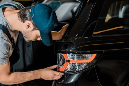 side view of young auto mechanic checking car back headlamp at auto repair shop