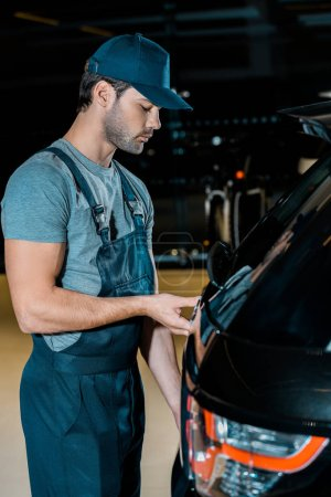 side view of young auto mechanic checking car trunk at auto repair shop