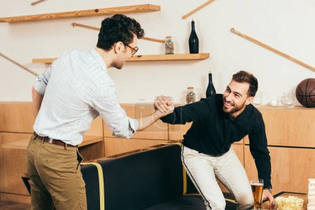 smiling friends shaking hands while greeting each other in cafe