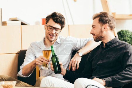 smiling friends clinking glass and bottle of beer in cafe