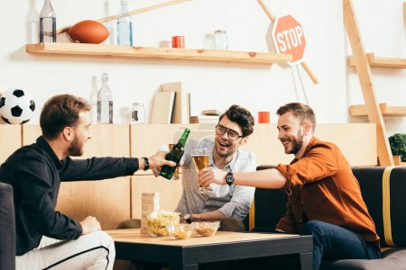 cheerful friends clinking drinks while resting in cafe together