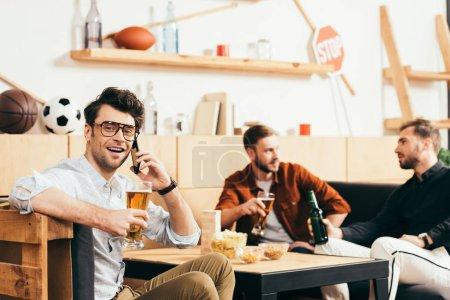 selective focus of man with beer talking on smartphone with friends behind in cafe