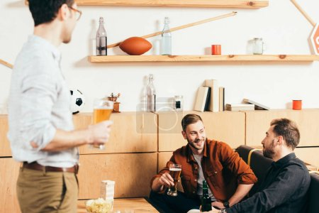 man with beer looking at smiling friends resting on sofa in cafe