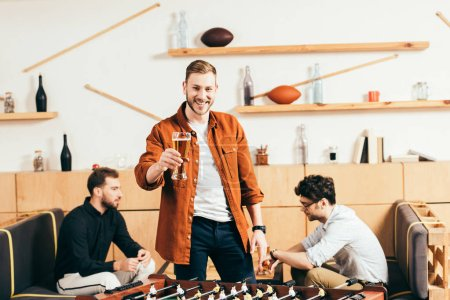 selective focus of smiling man with glass of beer standing at tablet football in cafe with friends behind
